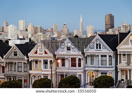 """Famous view of the """"Postcard Row"""" or """"Seven Sisters"""" Victorian Houses and downtown San Francisco viewed from Alamo Square park around dusk - stock photo"""