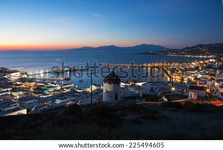 Famous windmills of Mykonos on the background of the night in the lights of the town. - stock photo