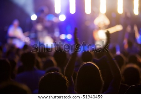 Fan cheering at live concert, some motion blur at arms, soft focus. - stock photo
