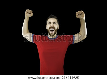 Fan in red and blue t-shirt celebrates on black background