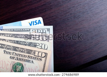 Fan of banknotes of dollars and credit card Visa, burgundy on  table, top view - stock photo