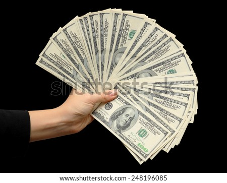 Fan of dollars in a female hand on a  black background - stock photo