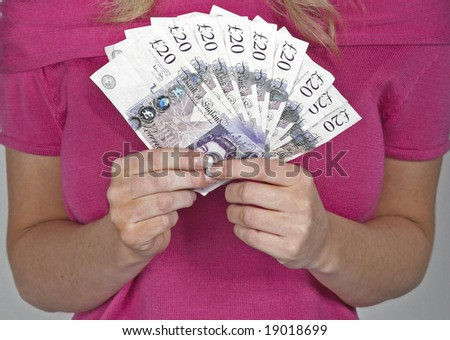 fan of £20 notes held by womens hands - stock photo