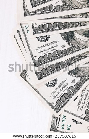 Fan of one hundred dollars banknotes lying on white wooden table, close up view - stock photo