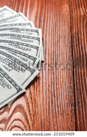 Fan of one hundred dollars banknotes lying on wooden table - stock photo