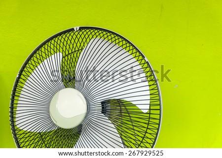 fan on green wall - stock photo