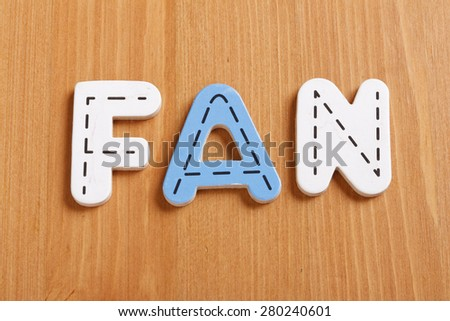 FAN, spell by woody puzzle letters with woody background - stock photo