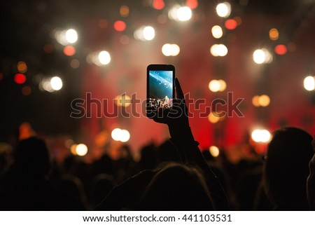 fan taking photo with cell phone at a concert - stock photo