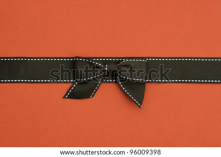 Fancy brown ribbon gift bow with white stitching on orange background - stock photo