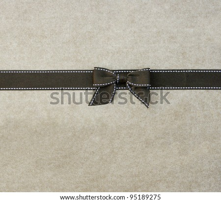 Fancy brown ribbon gift bow with white stitching on plain beige background - stock photo