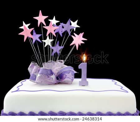Fancy cake with number one candle.  Decorated with ribbons and star-shapes, in pastel tones on black background.