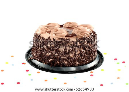 Fancy chocolate cake surrounded by confetti ready for a party isolated on a white background - stock photo