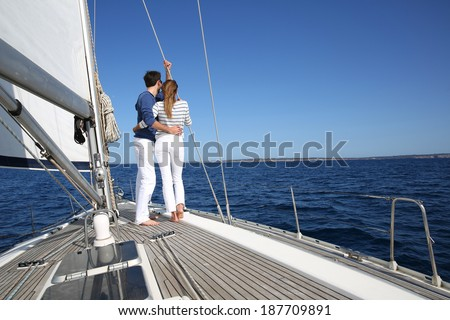 Fancy couple enjoying sailing on a beautiful sailboat - stock photo