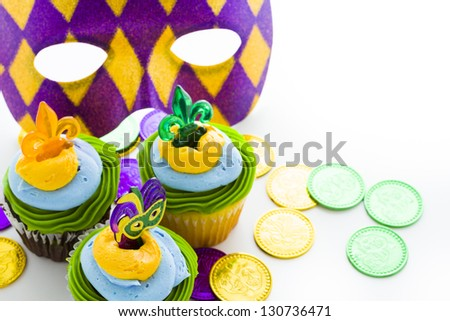 Fancy cupcakes decorated with leaf and mask for Mardi Gras party. - stock photo