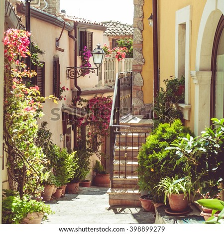 Fancy flower decorated narrow street in old town in summer sunshine, Sicily, Italy