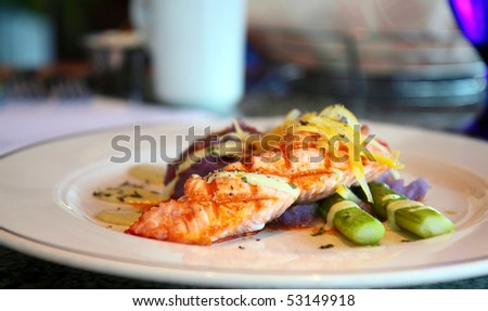 Fancy gourmet feast of grilled salmon, purple mashed potatoes, and asparagus - stock photo