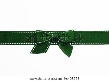 Fancy green ribbon gift bow with white stitching on white background - stock photo