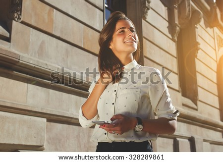 Fancy hipster girl is using smart phone, street look of female model with mobile phone. Strolling in a sunny weather with portable device. Photo is perfect with copy space area for your text message - stock photo