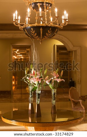 Fancy hotel lobby with chandelier and flowers. - stock photo