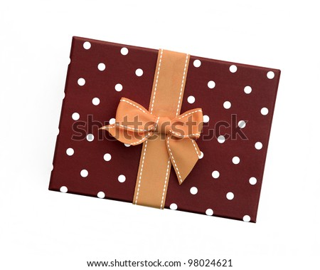 Fancy orange ribbon gift bow with white stitching on brown gift box with polka dots isolated on white background - stock photo