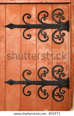 Fancy, ornate black iron hinges hold an old wooden door painted a garish red. - stock photo