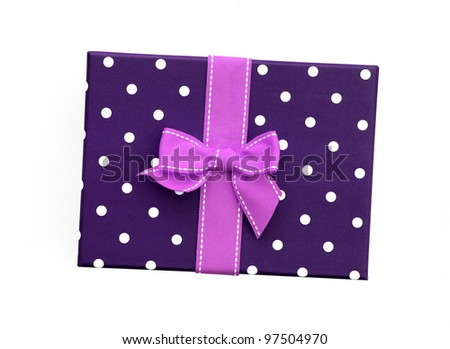 Fancy pink ribbon gift bow with white stitching on purple gift box with polka dots isolated on white background - stock photo