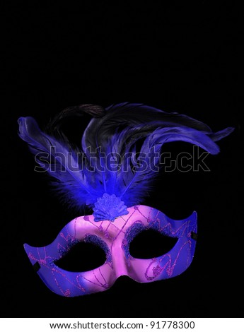 Fancy Purple and Blue Feathered Mask isolated on a black velvet background