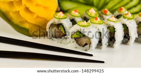 Tuna sushi roll with avocado and jalapeno pepper on a white plate