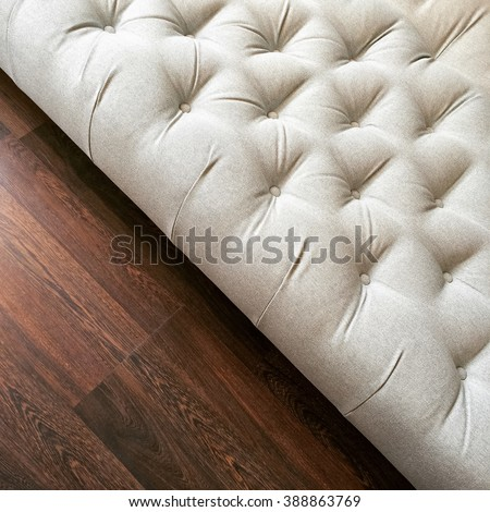 Fancy white ottoman on dark wooden floor. Classic style furniture.
