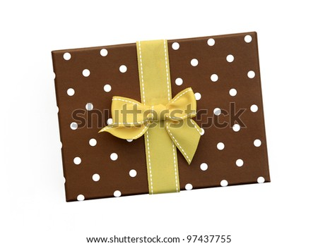 Fancy yellow ribbon gift bow with white stitching on gift box with polka dots isolated on white background - stock photo