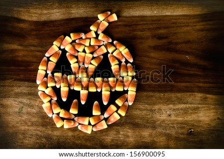 Fanged Halloween Jack-o-lantern made out of Candy Corn on top of a rustic harvest table.  Rustic grunge processing. - stock photo