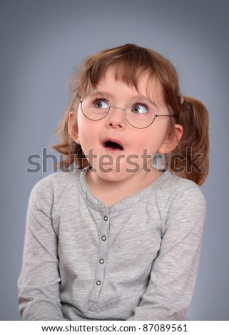Fanny little girl with glasses on grey background - stock photo