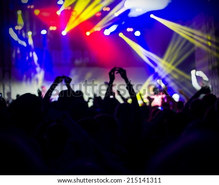 fans applauding to famous music band, nightlife, DJ on the stage in the club, crowd dancing on dance-floor, night performance