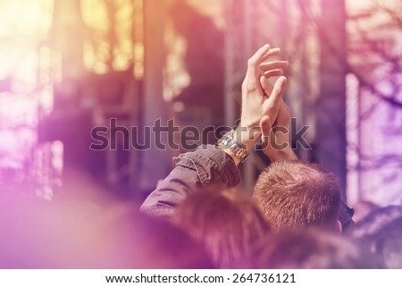 Fans Applauding To Music Band for Live Performing a Concert on Stage in Open Arena, Selective Focus Toned Image with Sunflares. - stock photo