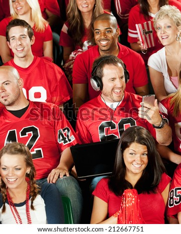 Fans: Guy At Football Game Busy Watching Electronic Device  - stock photo