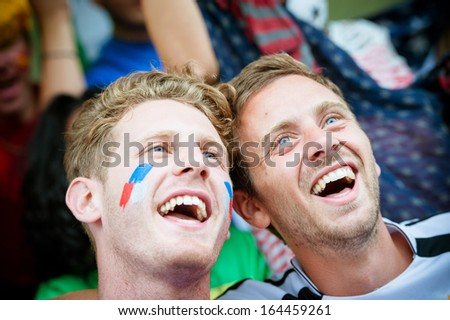 Fans of different nations at the stadium together - Stock Image - stock photo