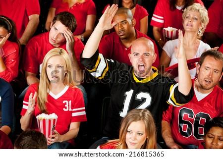 Fans: Opposing Football Team Fan Signals Touchdown - stock photo