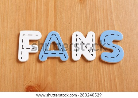 FANS, spell by woody puzzle letters with woody background - stock photo