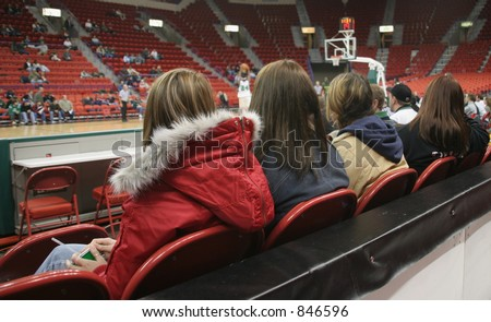 Fans watching a college basketball game - stock photo