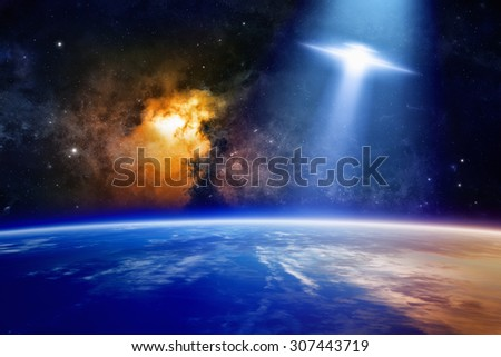 Fantastic background - ufo with bright spotlight approaches planet Earth in space, glowing nebula. Elements of this image furnished by NASA nasa.gov - stock photo