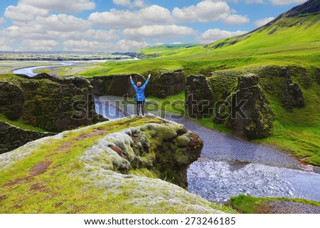 Fantastic country Iceland. Enthusiastic woman - tourist on a rock canyon  Fjadrargljufur - stock photo