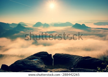 Fantastic dreamy sunrise on the top of the rocky mountain with the view into misty valley - stock photo