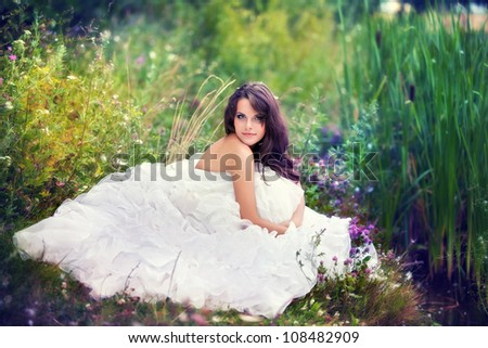 fantastic fairy bride in a green grass among flowers with closed eyes. - stock photo