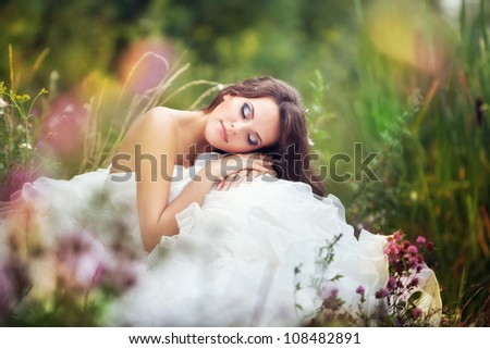 fantastic fairy bride in a wedding dress sits at green grass among flowers with closed eyes. - stock photo
