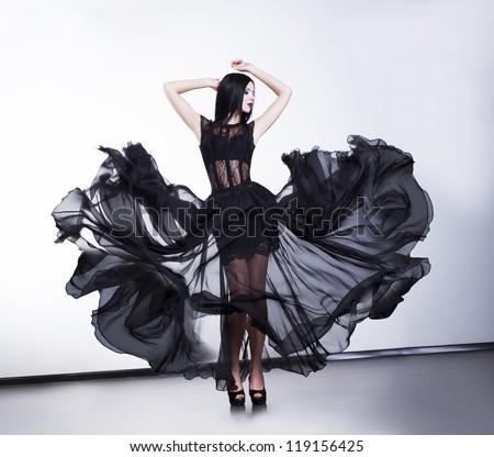 Fantastic fashion woman in fluttering black transparent dress - stock photo