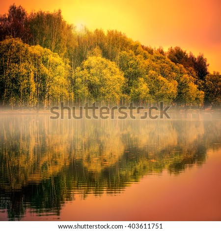 Fantastic Golden sunset over the misty lake with reflected in the water lush autumn trees - stock photo
