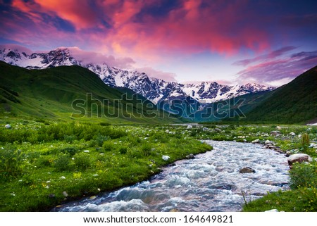 Fantastic landscape and colorful overcast sky at the foot of  Mt. Shkhara. Upper Svaneti, Georgia, Europe. Caucasus mountains. Beauty world. - stock photo