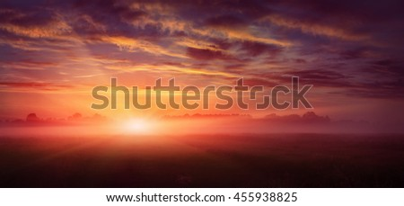 fantastic landscape. majestic misty morning over meadow. colorful sky with overcast clouds, under the influence of sunlight. dramatic picturesque scene. beauty of the world. creative images - stock photo