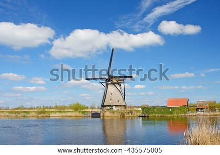 Fantastic landscape with windmills at the river against the background of the cloudy sky in Kinderdeyku, Holland