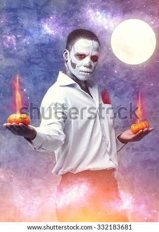 Fantastic man skeleton. The hero, a character at Halloween. The man in the role skeleton holding burning pumpkin. A poster for a party on Halloween. Voodoo people. Man is holding two orange pumpkin. - stock photo